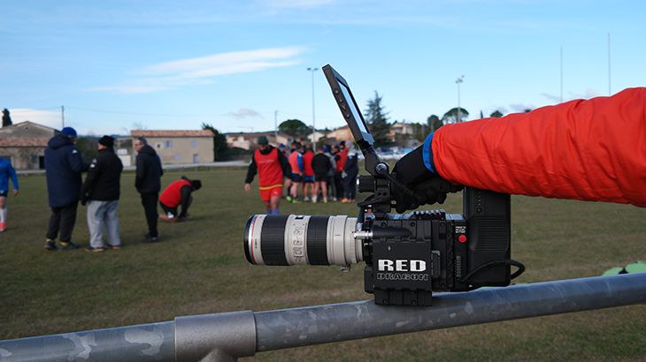 Close up of camera from the brand RED with the rugby field in the background.