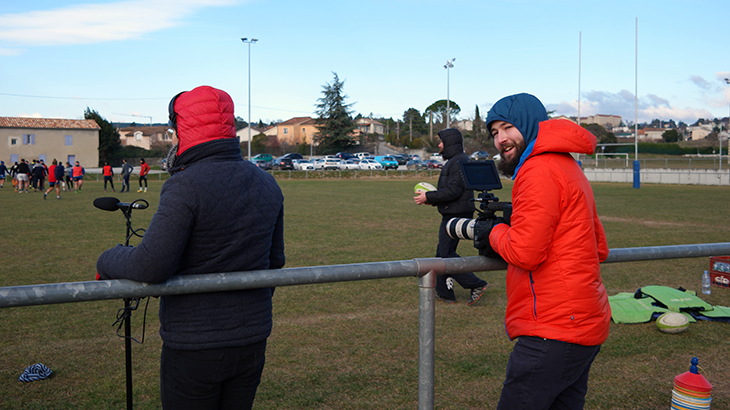 The camera team is trying to stay warm in the cold weather outside at the rugby field.